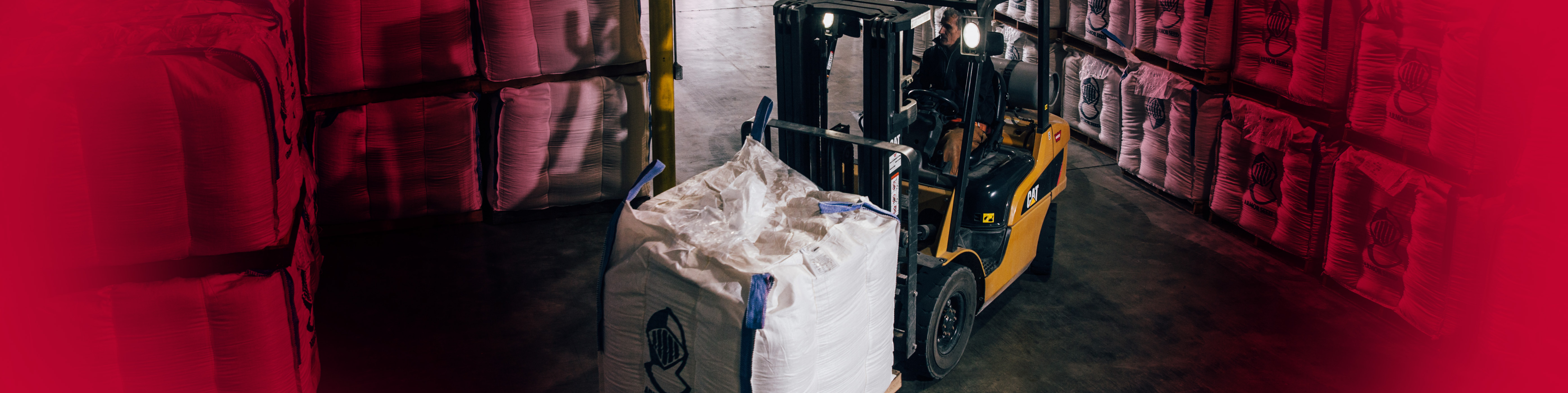 Forklift moving Armor Seed products in a warehouse.